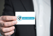 Image of a businessman holding a Care North East business card.